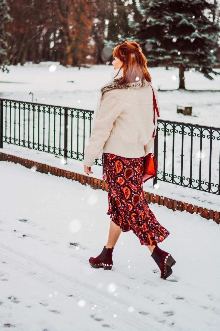Frau mit roten Chelseaboots SOFTCLOX Stiefeletten und Rock mit Paisley Muster auf verschneiter Brücke