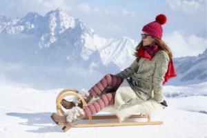 Frau mit Winteroutfit und SOFTCLOX Stiefeln auf einem Schlitten vor einer verschneiten Berglandschaft