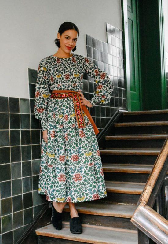 Clogs Styling im 70er Look. Frau mit Boho-Kleid und Clogs auf einer Treppe
