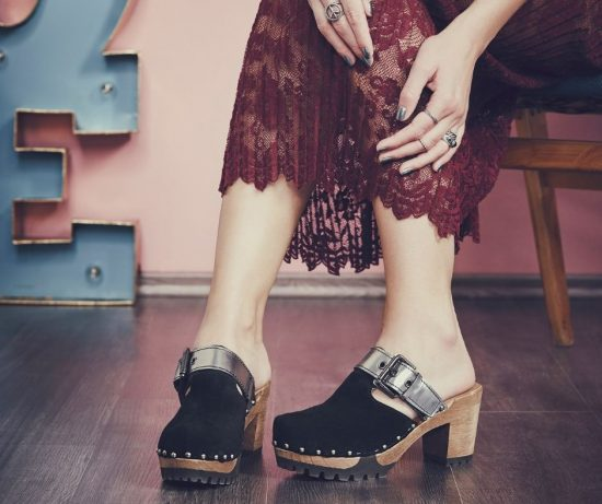 Beine einer Frau mit schwarz silbernen SOFTCLOX Clogs an den Füßen. Kombiniert mit einem roten Spitzenrock.